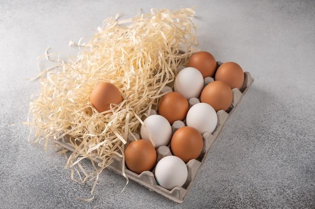 밝은 질감 배경에 종이와 짚에서 친환경 패키지에 갈색과 흰색 닭고기 달걀.