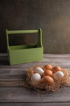 나무 바탕에 짚 둥지에 갈색과 흰색 닭고기 달걀. 나무 상자 뒤에.