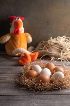 나무 바탕에 짚 둥지에 갈색과 흰색 닭고기 달걀. 닭 장난감 옆. 소박한 스타일. 공간 복사