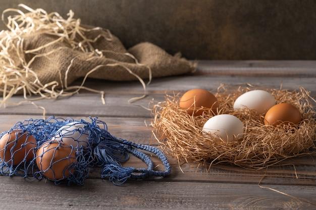나무 바탕에 짚 둥지에 갈색과 흰색 닭고기 달걀. 에코 스트링 가방 옆에 계란이 들어 있습니다. 소박한 스타일. 공간 복사