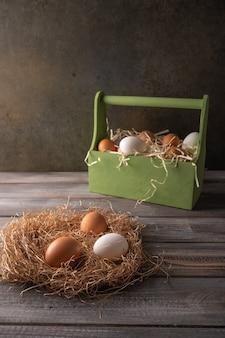 나무 바탕에 짚 둥지에 갈색과 흰색 닭고기 달걀.