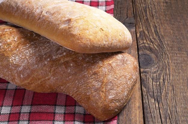 오래 된 나무 테이블에 갈색과 흰색 ciabatta 빵