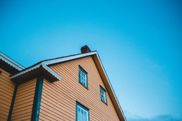 昼間の青空の下で茶色と白のコンクリートの家