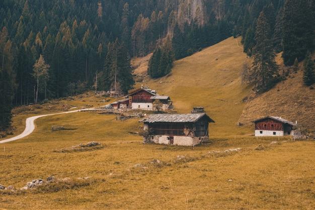 Коричнево-белый дом на поле зеленой травы возле коричневой горы в дневное время
