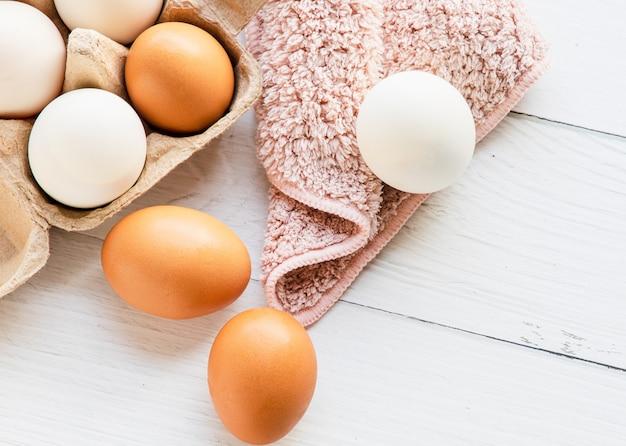 白い木製のテーブルの上に置かれた茶色の紙箱に入った茶色と白の有機鶏卵。卵は健康愛好家に適したタンパク質を提供します。上面図とコピースペース