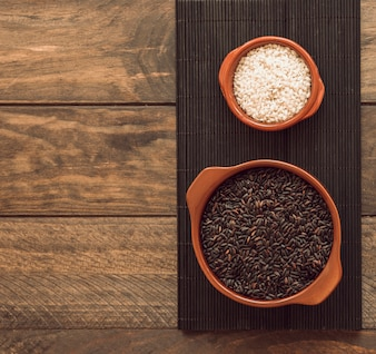 Brown and white rice grains in the bowl on tray over the wooden table