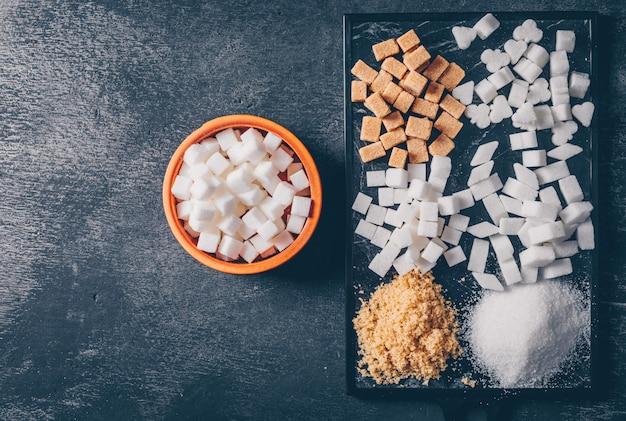 Коричневый и белый сахар в разделочную доску и миску. плоская планировка
