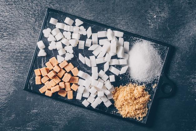 Коричневый и белый сахар в разделочной доске плоской кладки