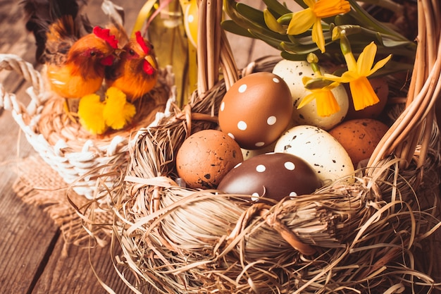 Коричневые и желтые яйца в корзине, пасхальные украшения