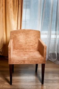 창 옆에 갈색 안락 의자.