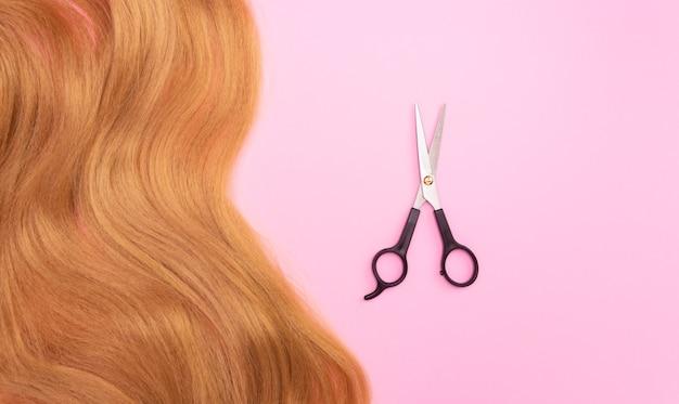 Коричневые искусственные волосы на розовой поверхности и ножницы