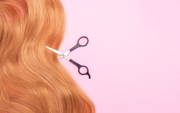 Brown artificial hair on pink and scissors