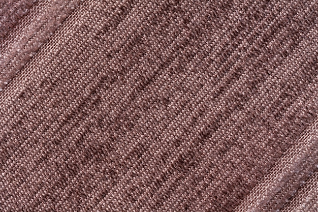 Brown background of a knitted textile material. fabric with a striped texture closeup.