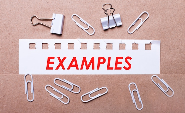 On a brown background, white paper clips and a torn strip of white paper with the text examples