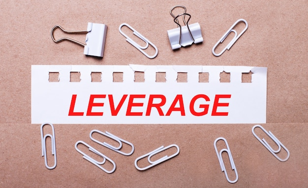 On a brown background, white paper clips and a torn strip of white paper with the text leverage