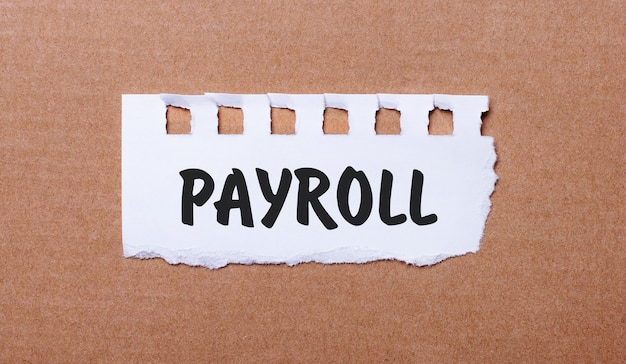 On a brown background, white paper with the inscription payroll