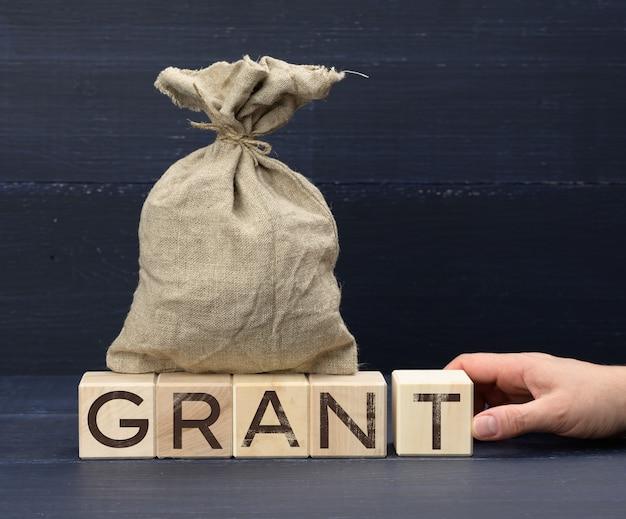 Коричневая сумка полная и деревянные кубики с надписью grant
