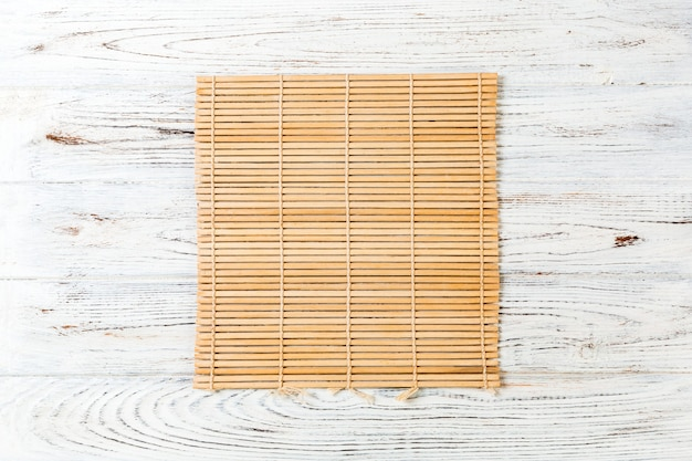 Brown bamboo mat on white wooden