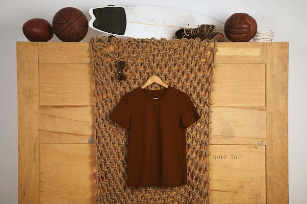 Brown basic cotton t-shirt presented in rustic interior with vintage leather play balls on top
