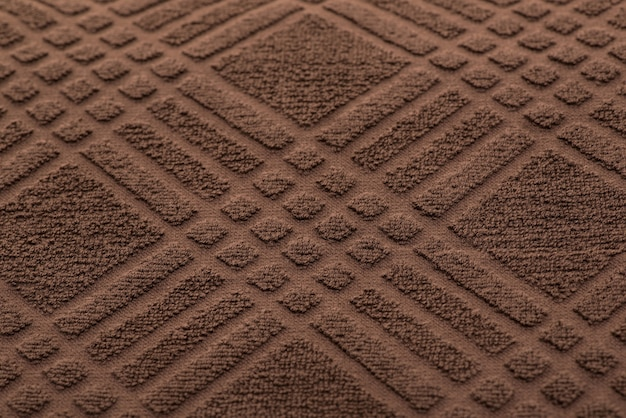 Brown bath towel in a cage. textured fabric background