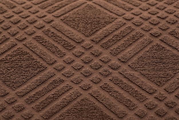 檻の中の茶色のバスタオル。テクスチャード生地の背景