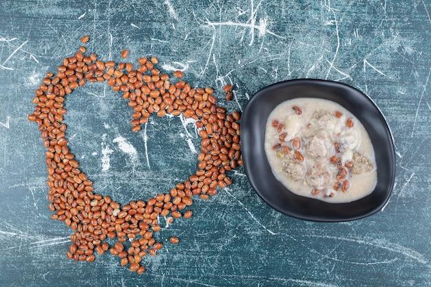 Коричневая фасоль и грибной суп на синем фоне. фото высокого качества