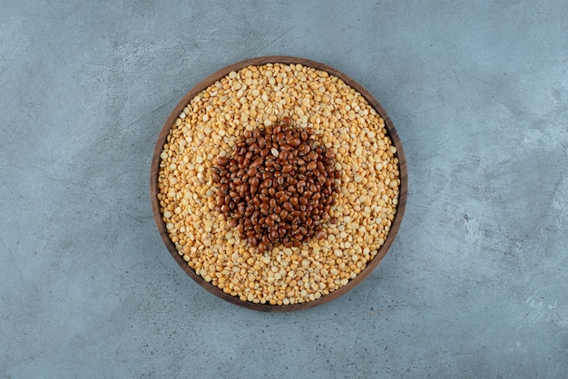 Коричневая фасоль и горох на деревянном блюде. фото высокого качества
