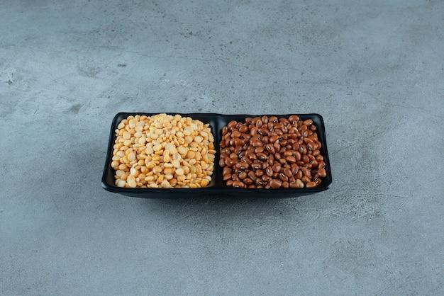 Fagioli e piselli marroni in un piatto nero. foto di alta qualità