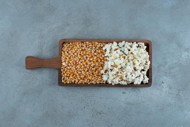 Fagioli marroni e popcorn su un piatto di legno. foto di alta qualità