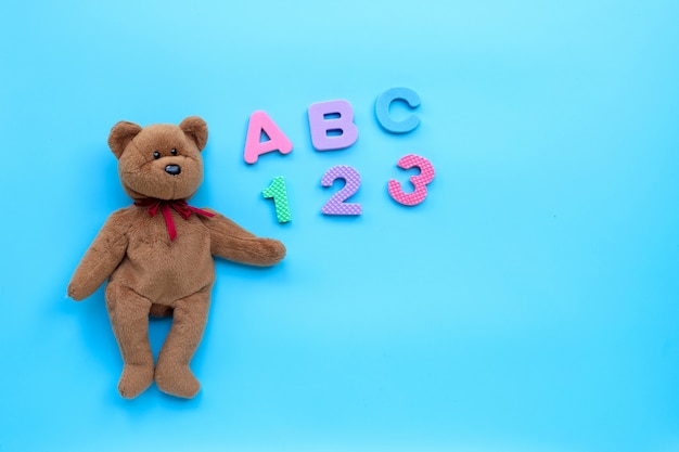 Brown bear toy with english alphabet and numerals on blue background. education concept