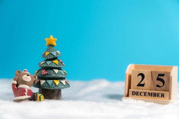 Бурый медведь в новогодней шапке сидит возле елки и календаря из деревянных блоков