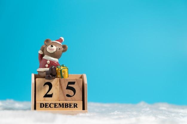 Бурый медведь в шляпе рождество, сидя на деревянный блок календарь, установленный на рождество d