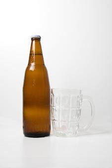 Brown beer bottle with empty beer glass
