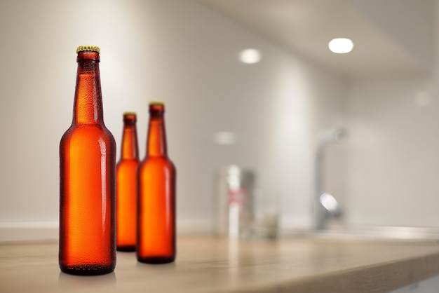 Brown beer bottles on kitchen table mockup. no label, water drops.