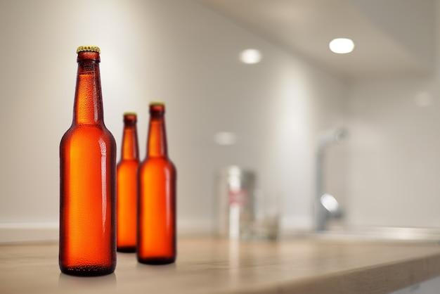 台所のテーブルのモックアップに茶色のビール瓶。ラベルなし、水滴。