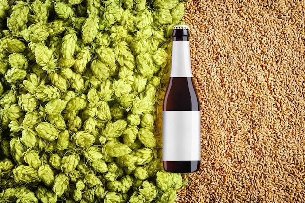 홉 콘과 밀 곡물 배경에 갈색 맥주 bottlle 모형. 유리에 회색 라벨이 있습니다. 보기의 상단. 디자인을위한 준비 템플릿입니다.