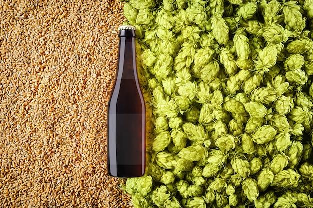 홉 콘과 밀 곡물 배경에 갈색 맥주 bottlle 모형. 유리에 반투명 라벨이 있습니다. 보기의 상단. 디자인을위한 준비 템플릿입니다.