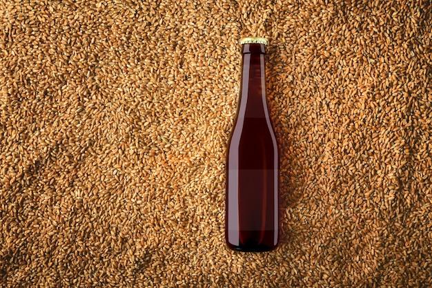 현실적인 그림자와 반투명 라벨에 반사와 밀 곡물 배경에 갈색 맥주 유리 병 모형. 보기의 상단. 디자인을위한 준비 템플릿입니다.