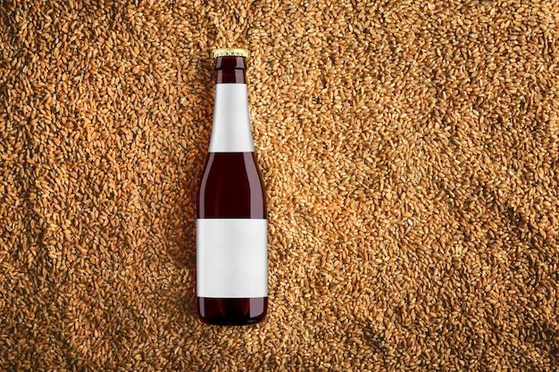 현실적인 그림자와 회색 라벨에 반사와 밀 곡물에 갈색 맥주 유리 병 모형. 보기의 상단. 디자인을위한 준비 템플릿입니다.
