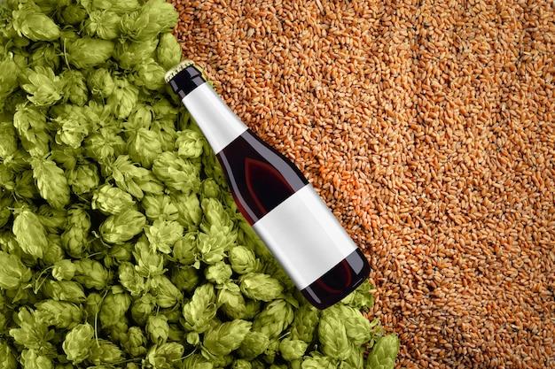 밀 곡물 및 홉 배경에 대각선 배치 bottlle와 갈색 맥주 모형. 유리에 회색 라벨이 있습니다. 디자인을위한 준비 템플릿입니다.