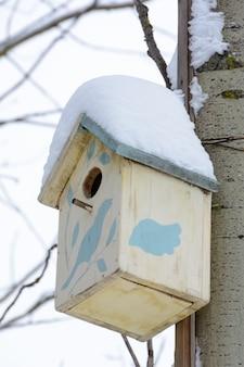 Коричневый скворечник на дереве. деревянный скворечник ручной работы, покрытый снегом. зимний пейзаж с деревьями, покрытыми снегом.