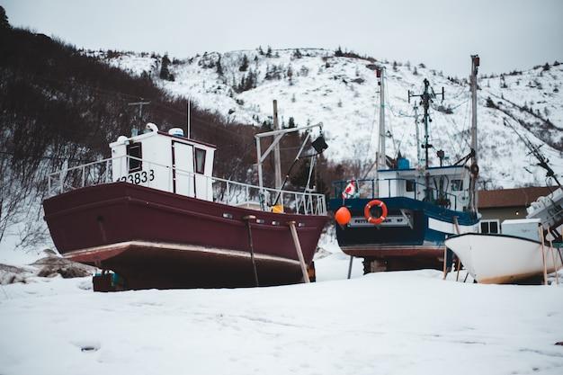 昼間の雪に覆われた地面に茶色のボート