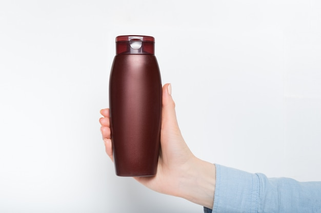 Brown bottle for cosmetic in a female hand.