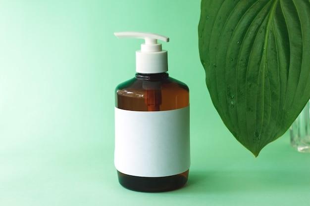 緑のギボウシの葉で製品を入浴するための茶色のボトルのモックアップ