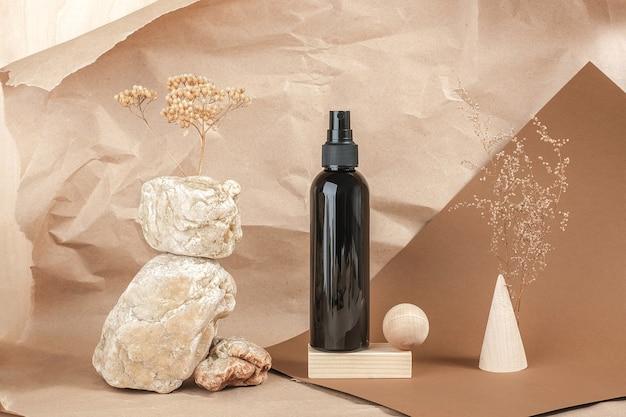 Коричневая бутылка косметических продуктов на камне, деревянные геометрические фигуры на бежевой бумажной предпосылке. натуральный органический спа-салон косметическая концепция красоты вид спереди.