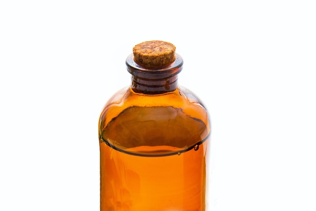 Brown bottle with essential oil on white surface