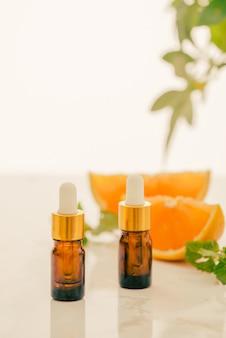 白い背景にレモン、オレンジ、タンジェリン、ビタミンcの茶色のボトル。