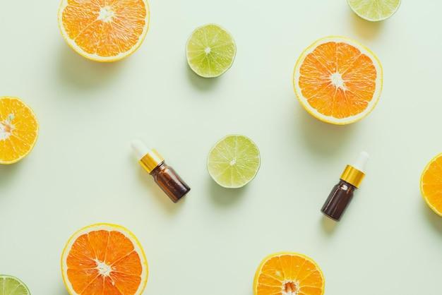 Коричневая бутылка с лимоном, апельсином, мандарином и витамином с на белом фоне.