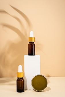 흰색 연단 크림 배경에 천연 스킨 케어 화장품 스파 액세서리에 대한 갈색 병 모형