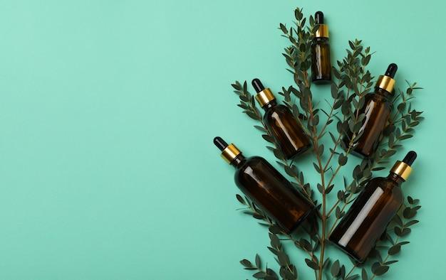 Коричневые бутылки эвкалиптового масла и ветки на фоне мяты